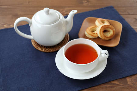 cup of tea with ring scone biscuit on plate with isolated on table 写真素材