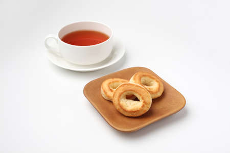 ring scone biscuit on plate with hot tea isolated on white background