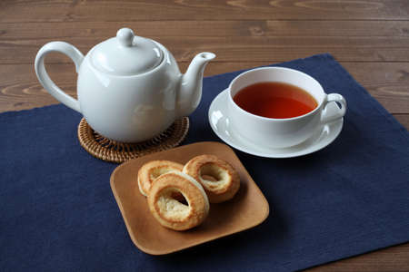 ring scone biscuit on plate with hot tea isolated on table