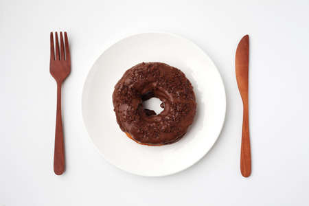 chocolate frosted doughnut on plate closeup isolated on white background 写真素材