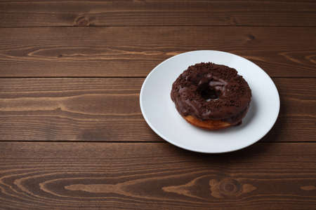 chocolate frosted doughnut on plate closeup isolated on wooden table