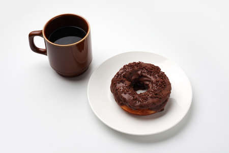 chocolate frosted doughnut on plate with hot coffee closeup isolated on white background 写真素材