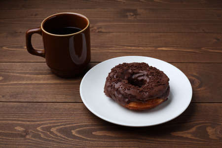 chocolate frosted doughnut on plate with hot coffee closeup isolated on wooden table