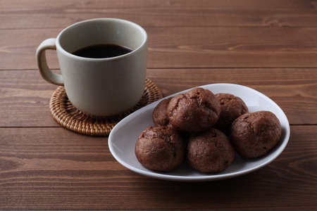 chocolate cream puffs on plate with hot coffee closeup isolated on wooden table