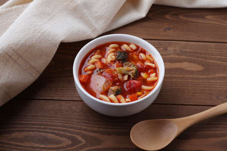 minestrone vegetables tomato soup with pasta closeup isolated on wooden table Banque d'images