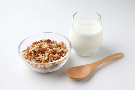 granola cereal in bowl with milk closeup isolated on white background Stock Photo