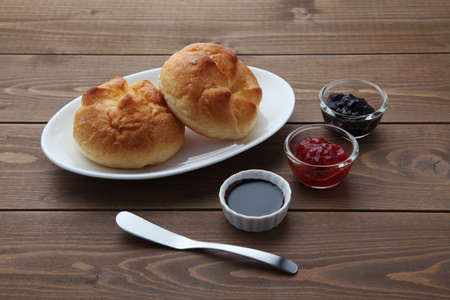 butter bread roll on a plate with strawberry jam on wooden table