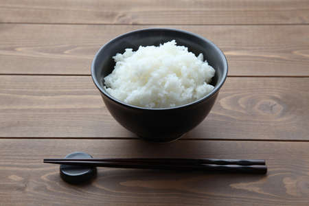 plain white rice in bowl with chopsticks isolated on table