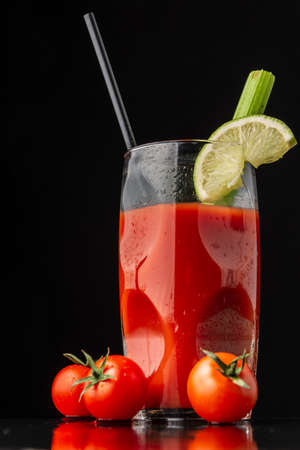Close-up view of Bloody Mary cocktail glass with lime, celery and straw, on slate with cherry tomatoes, selective focus, on black background in vertical