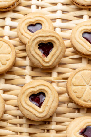 Close-up of heart-shaped cookies and strawberry jam, on a basket, for Valentine's Day, in vertical