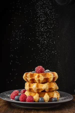 Top view of stacked waffles with raspberries and blueberries on dark plate, with sugar falling, on wooden table, black background, vertical