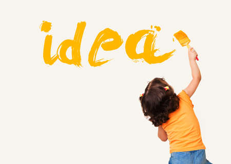 painting on the wall: Cute little girl writing Idea with painting brush on wall background
