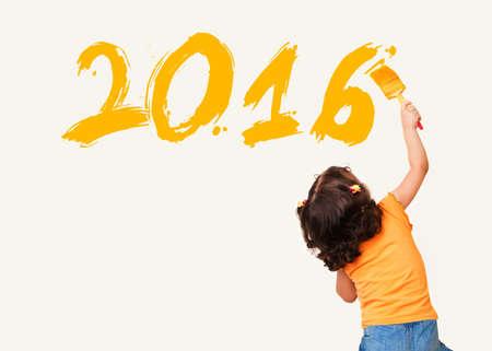 dessin enfants: La petite fille mignonne de dessin nouvelle ann�e 2016 avec un pinceau de peinture sur le mur de fond Banque d'images