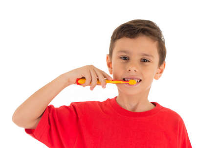 beautiful little boys: Young boy feeling happy and brushing his teeth, wearing red t-shirt , isolated on white background