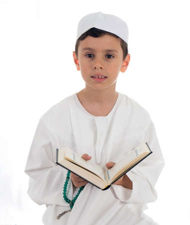 islamic pray: Muslim young boy reading Quran - isolated on white background Stock Photo