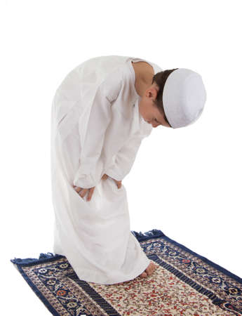 islamic pray: Muslim young boy praying on a carpet isolated on white background