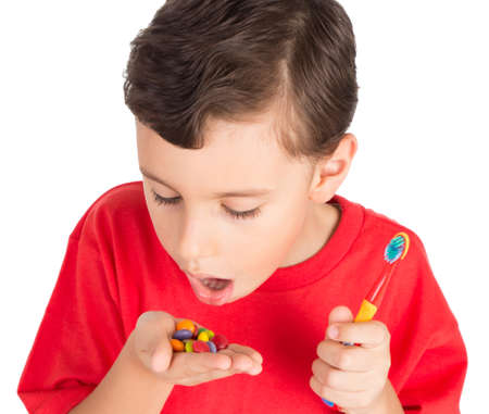 oral care: Young boy going to eat candies with teeth brush ready in his hand Stock Photo