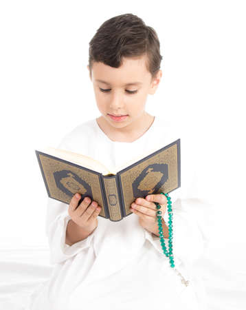 child hand: Muslim young boy reading Quran and holding rosary - high key