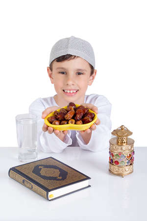 Little Muslim kid smiling while presenting a dish of dates for iftar - breaking fast in Holy Ramadan - showing generosity of Ramadan