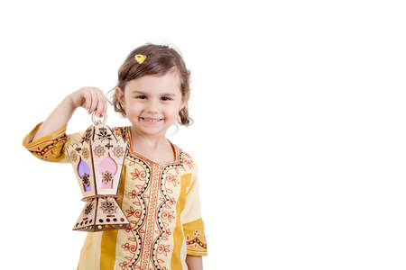 Ramadan Kareem - Young girl smiling and holding Ramadan lantern