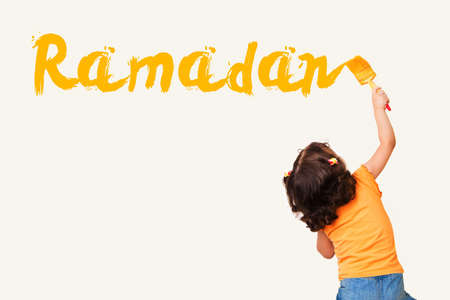 Cute little Muslim girl drawing Ramadan with painting brush on wall background Standard-Bild