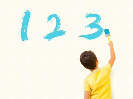 smart boy: Smart little boy learning math and writing numbers 123 with painting brush on wall background Stock Photo