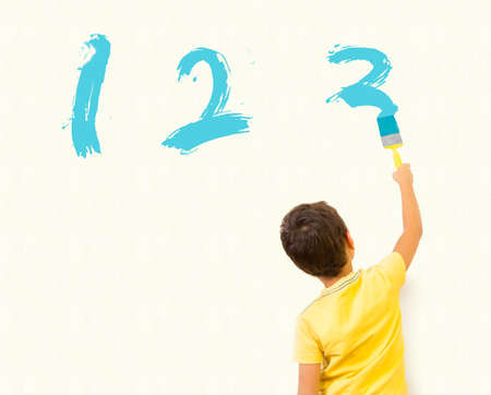 smart boy: Smart little boy learning math and writing numbers 123 with painting brush on wall background  - Almost Finished