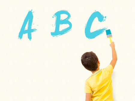 smart boy: Smart little boy learning English and writing alphabet letters ABC with painting brush on wall background Stock Photo