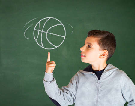 School boy with hand drawn basketball on green chalkboard