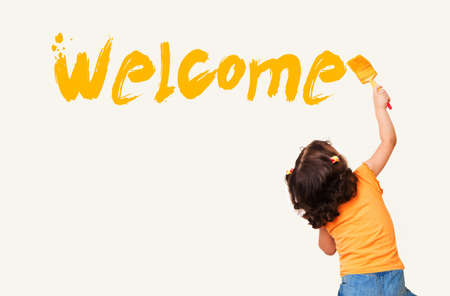 Cute little girl writing Welcome with painting brush on wall background