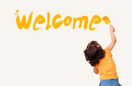"""Schattig klein meisje het schrijven van """"Welkom"""" met het schilderen van borstel op muur achtergrond"""