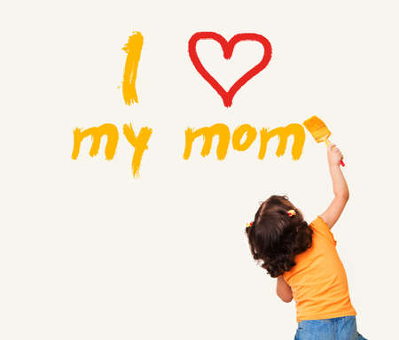 love mom: Little girl writing I Love my mom with painting brush on wall background Stock Photo