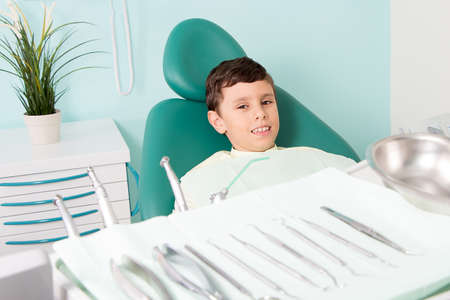 Little cute kid smiling while sitting in chair at dental clinic