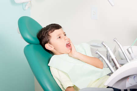 Little cute kid feeling pain while sitting in chair at dental clinic Standard-Bild