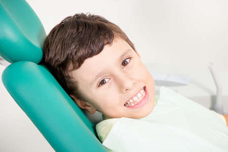 Little cute kid smiling - showing his teeth - while sitting in chair at dental clinic