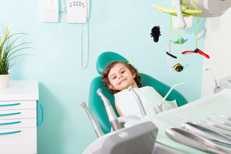Little cute girl smiling while sitting in chair at dental clinic Standard-Bild