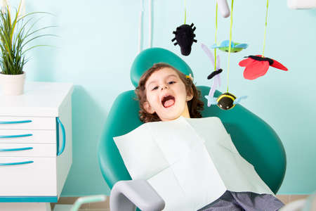 Little cute girl sitting in chair at dental clinic - ready for dentist examining her teeth Standard-Bild