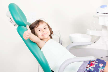 Cute little girl smiling showing Ok sign ( thumb up ) at dental clinic