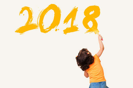 Cute little girl drawing new year 2018 with painting brush on wall background