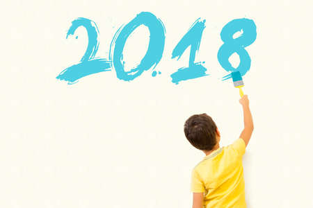 Cute little boy drawing new year 2018 with painting brush on wall background Standard-Bild
