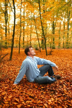 man in autumn park on cover from leafs photo