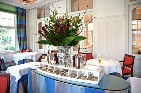flowers and table with silver in classic restaurant photo