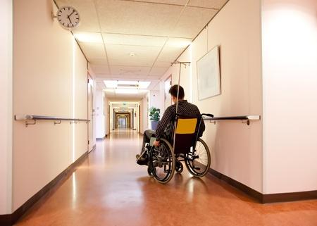 sick person: hombre en silla de ruedas en el pasillo del hospital vac�o