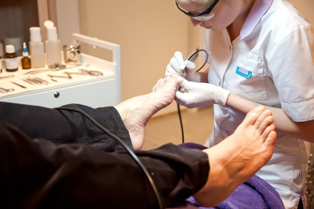 man in salon for medical pedicure photo