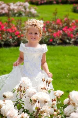 hair dress: ni�a con vestido blanco en el jard�n de rosas  Foto de archivo