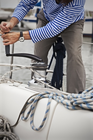 yacht people: Sailor pulling rope on yacht