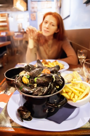 mussels pan in seafood restaurant and women at table  photo