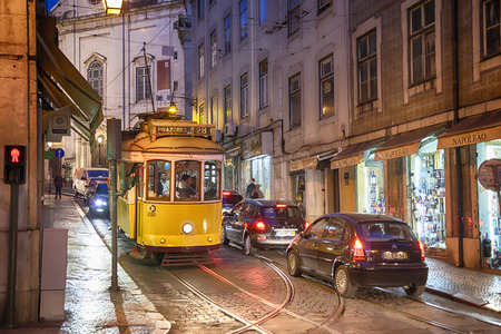 typical yellow tram of Lisbon near Rua da Madalena, Portugal in old historical city, mart 2014