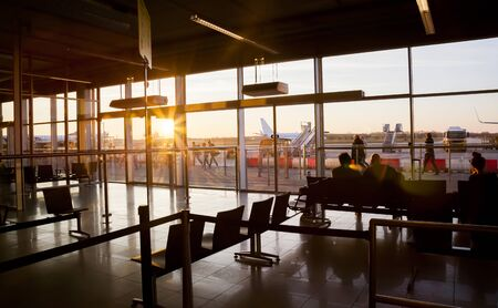 arrival departure board: Silhouette of airline passengers in an Eindhoven airport lounge by sunset