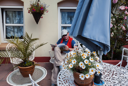 man reading magazine in home garden, front door photo